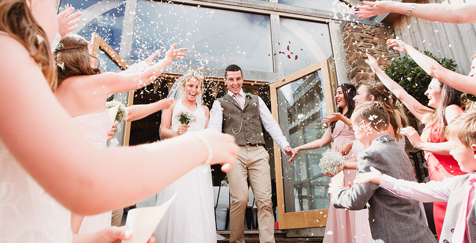 Confetti thrown at couple exiting the Cider Barn