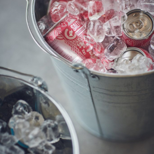 Soft drink cans on ice in a metal pail