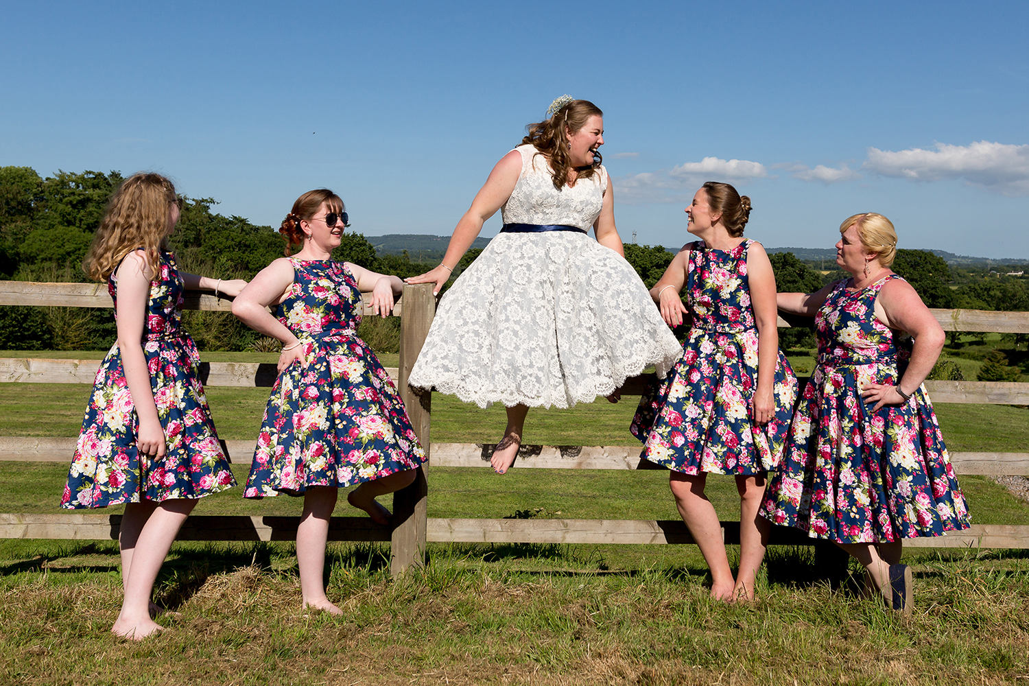 Bride and bridesmaids sitting on fence with view