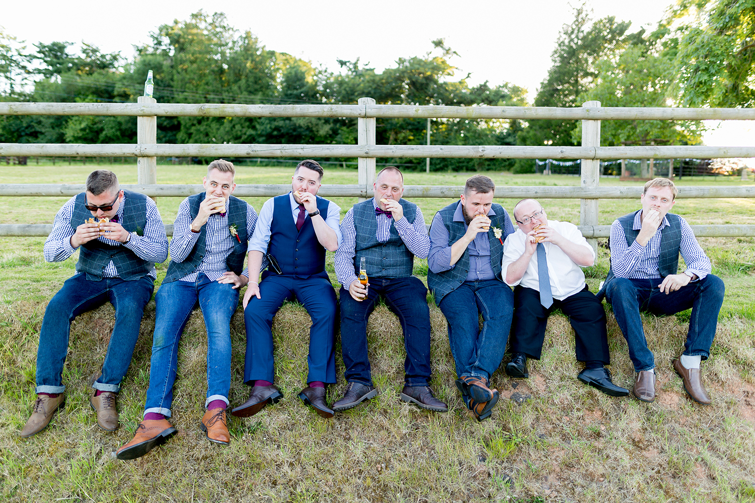 Grooms mens seated eating burgers and drinking beer