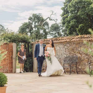 Bride and father entering the walled garden