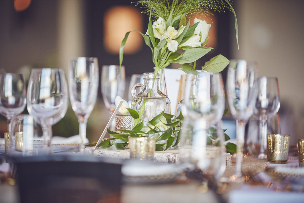 Close up of flowers and wine glasses  set up on wedding table