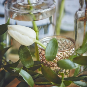 Close up of vase, flowers and votive on wedding table