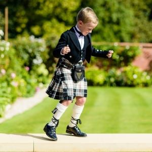 Child in kilt dancing in walled garden