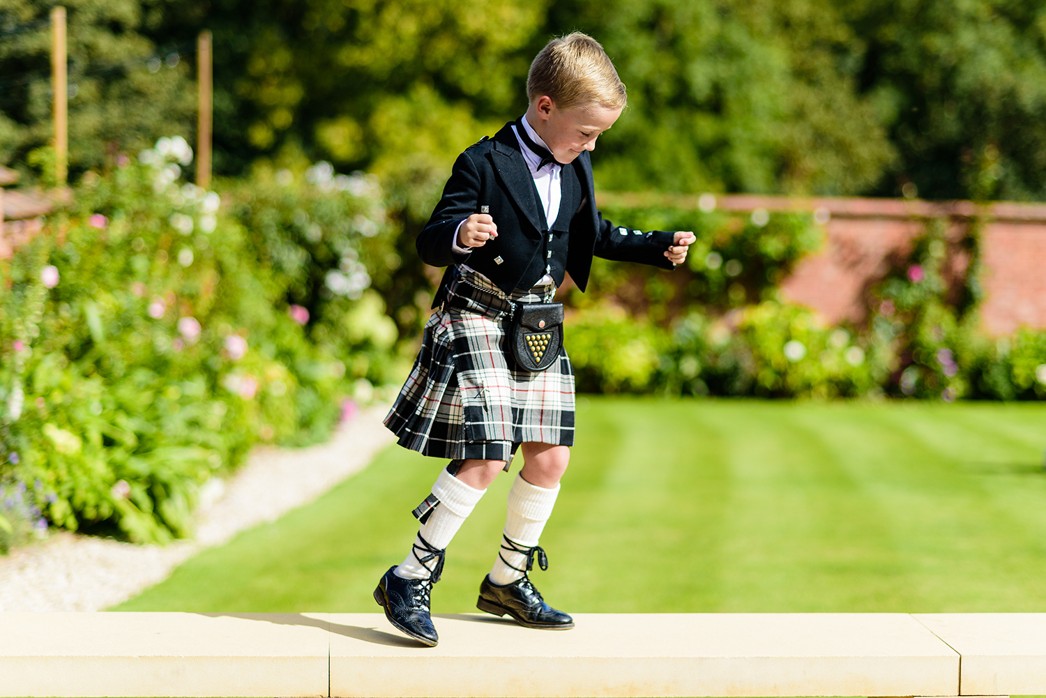 Child in kilt dancing in walled garden