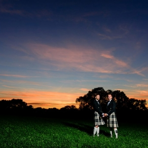 Newly wed male partners hold hands at dusk