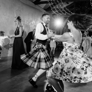 Groom spinning and dancing wildly with wedding guest