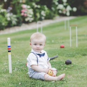 Toddler next to a croquet set on lawn