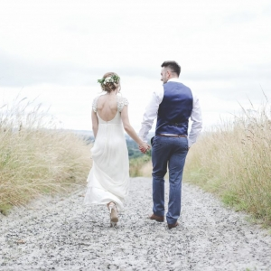 Newlyweds walk in the fields
