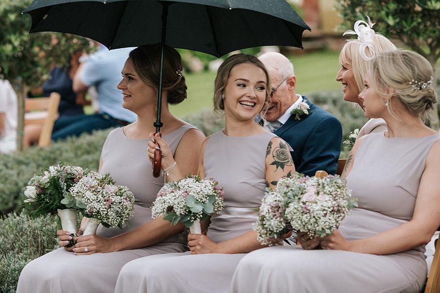 Bridesmaids smiling through the rain