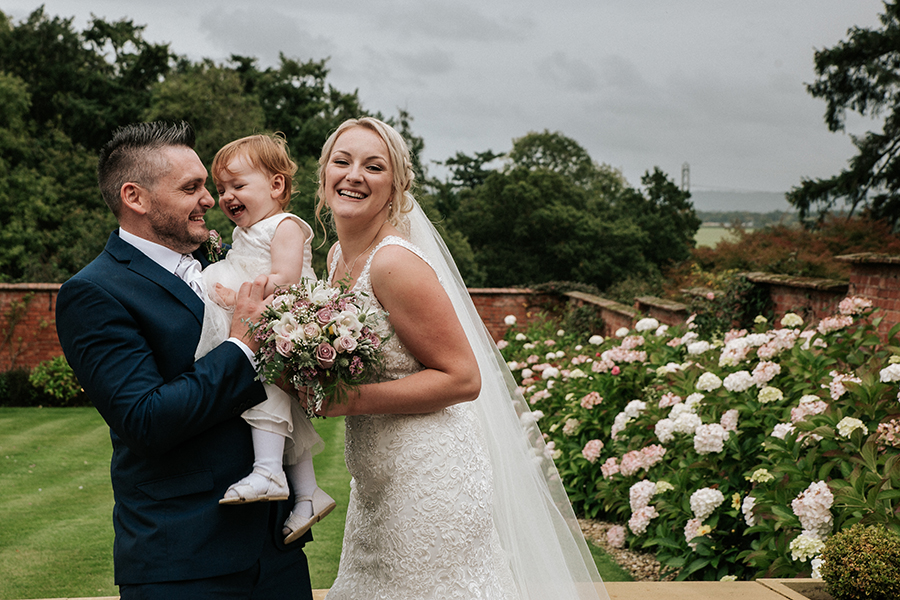 Happy wedding couple with daughter in the garden