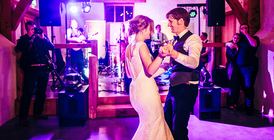 Couples first dance in cider barn in front of band