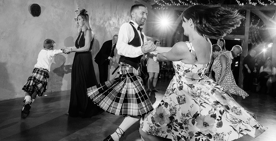 Kilted groom dances with guest