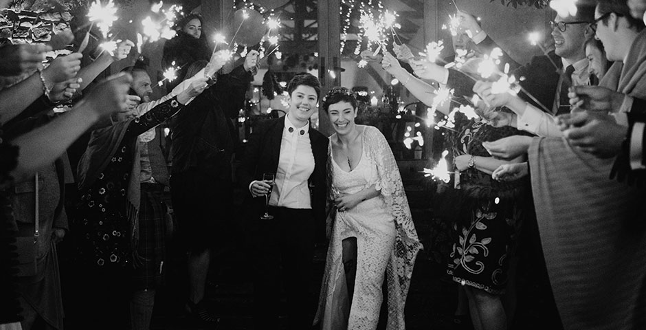 Archways of sparklers indoors for the same sex wedding