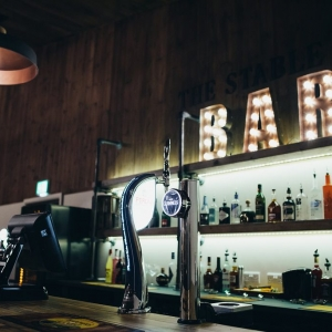 Bar with light up sign in rustic barn