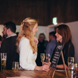 Female guests chat at the bar with drinks