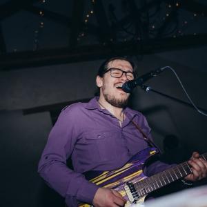 Band member sings and plays guitar