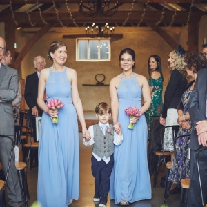 Bridesmaids and Page Boy walk the aisle