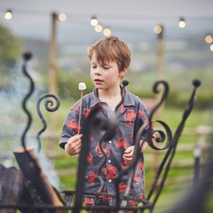 Boy with marshmellow on a stick by the fire pitts