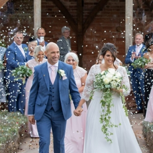 Bride and groom covered in confetti while walking back up the aisle in the walled garden