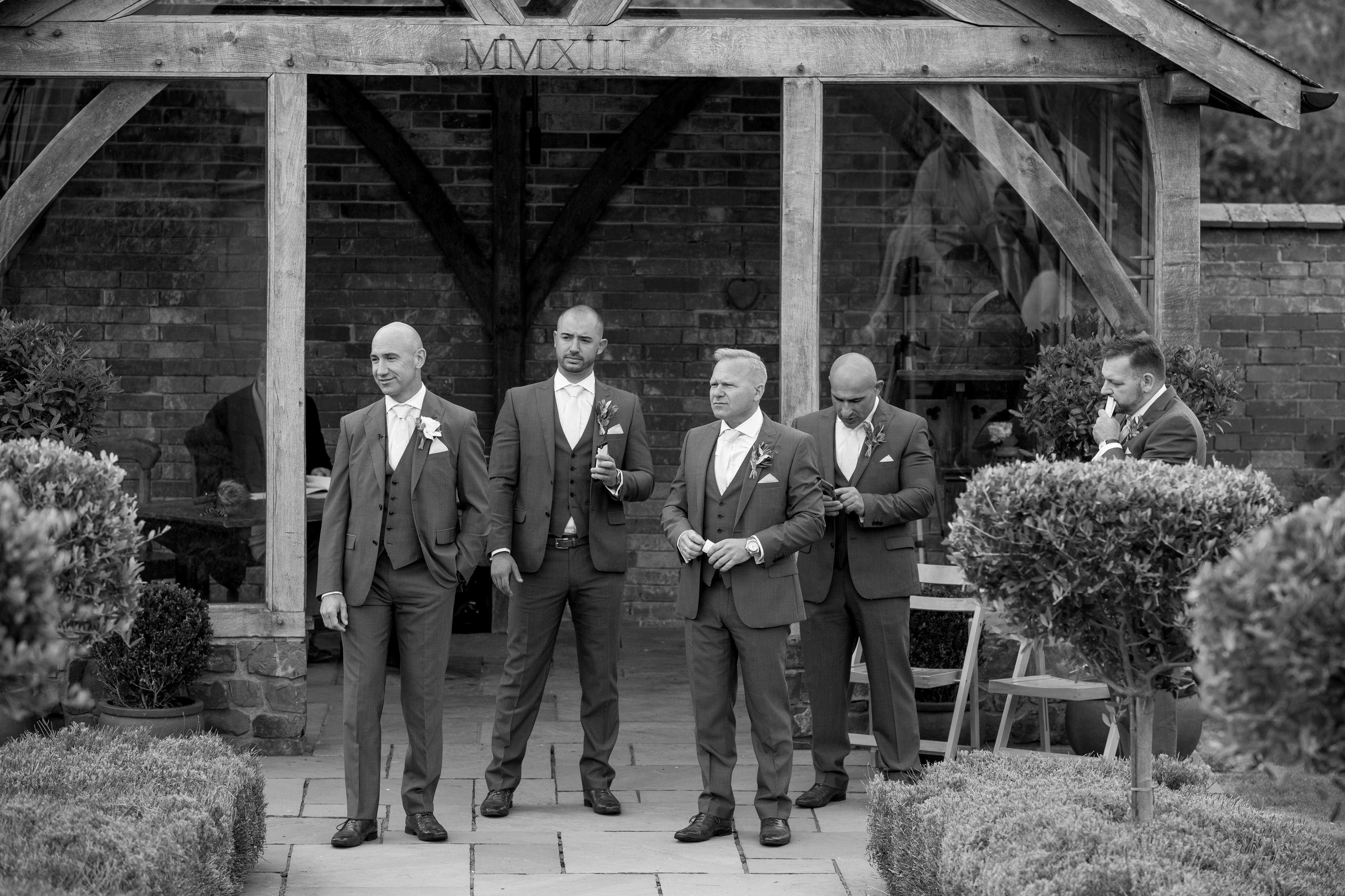 Grooms men await arrival of bride at the arbor