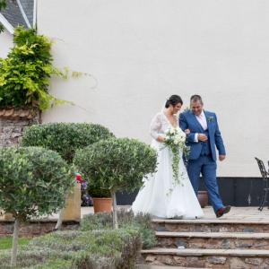 Bride is walked by her father to the aisle in the walled garden