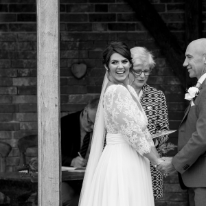 Bride smiles while exchanging vows in the walled garden arbor