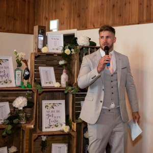 Grooms man welcomes guests to the wedding breakfast