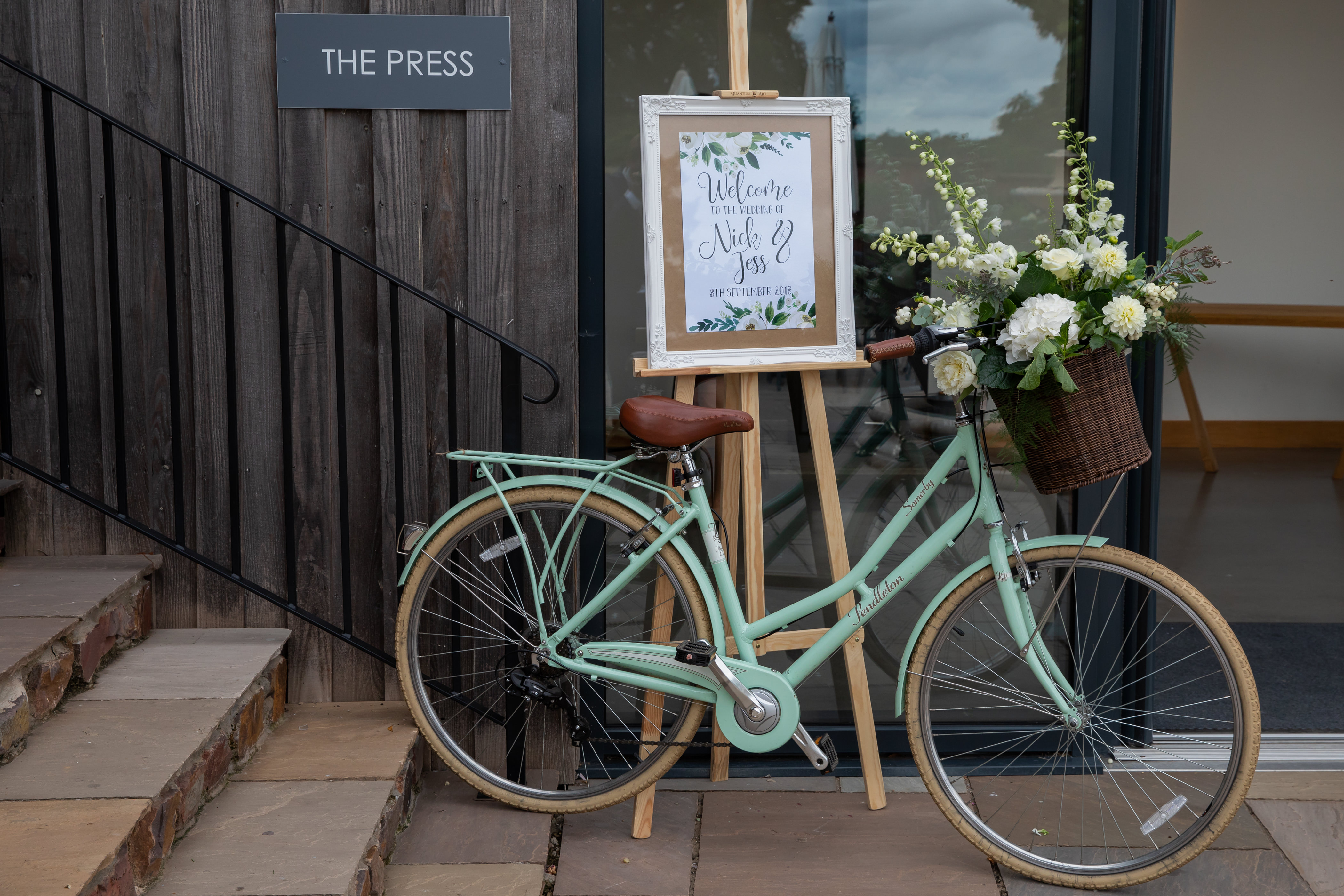 Welcome sign on easel next to bicycle by The Press Bar