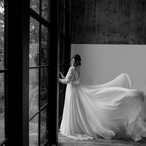 Brides dress bellows by tall sunlit window