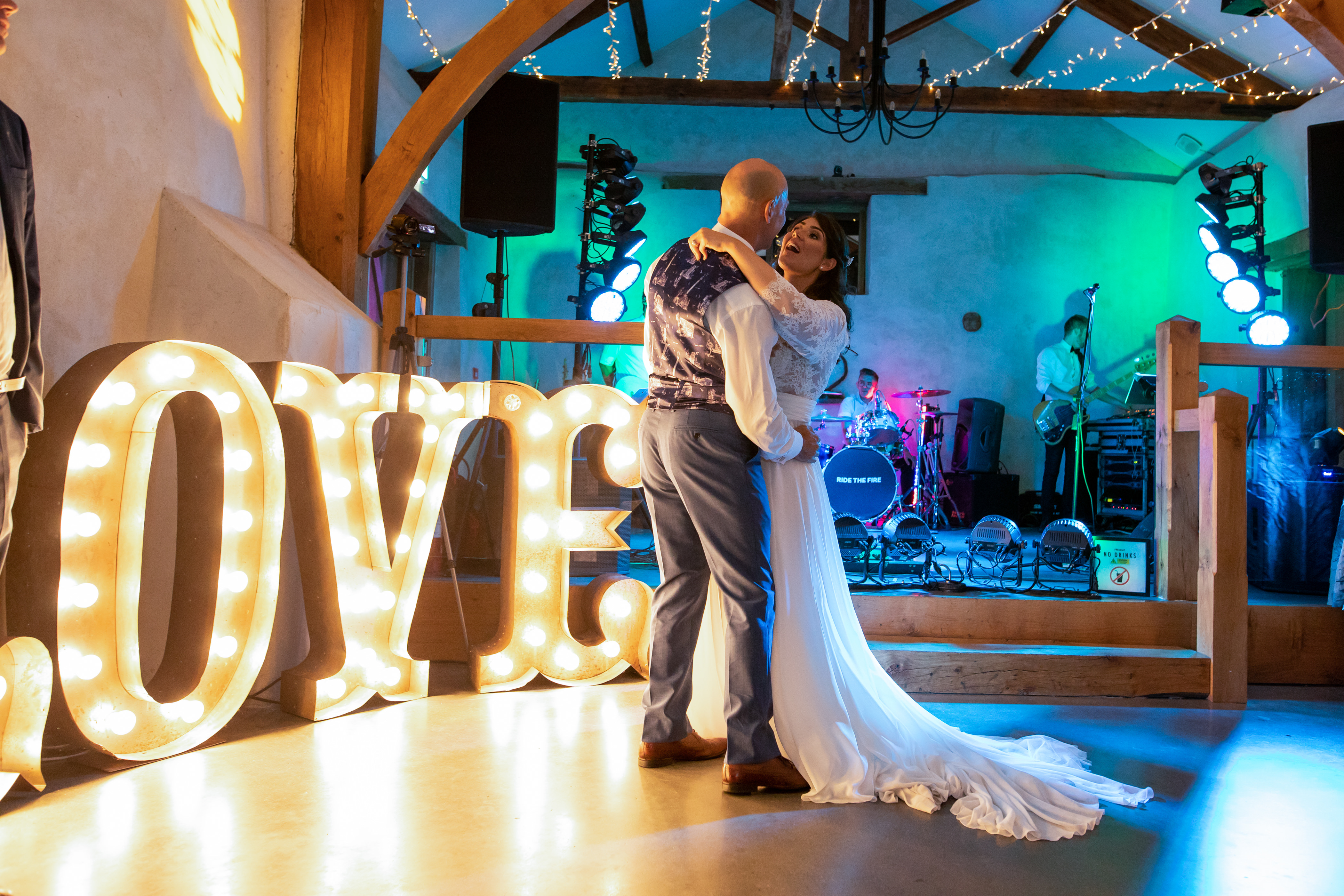 Bride and Groom dance by large LOVE letters in The Cider Barn