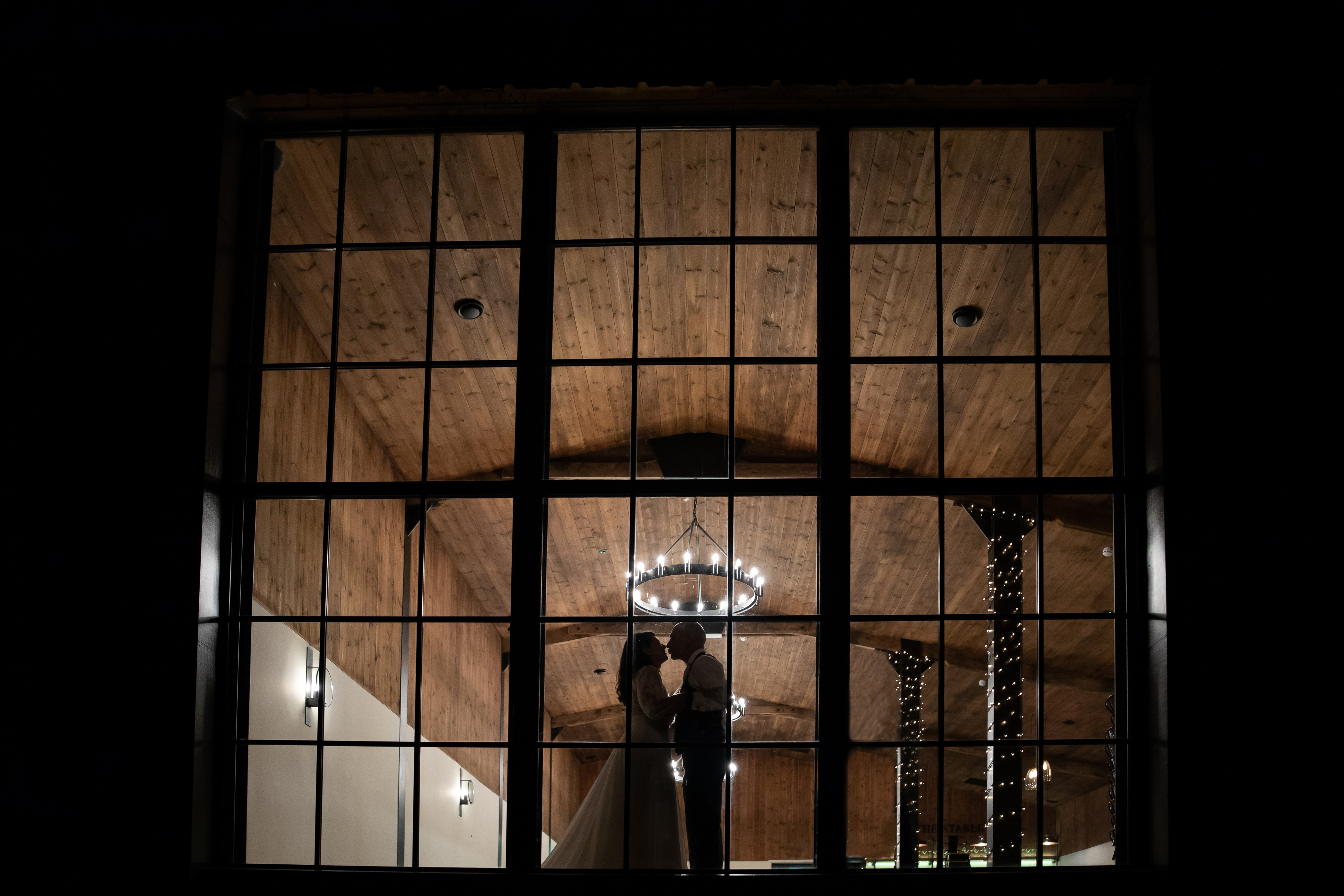 Bride and Groom sihouetted by lights in The Stable barn large window.