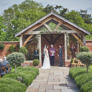 Couple exchanging vows in the arbour