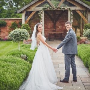 Bride and Groom walking towards the arbor
