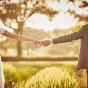 Bride and groom holding hands in field at sunset