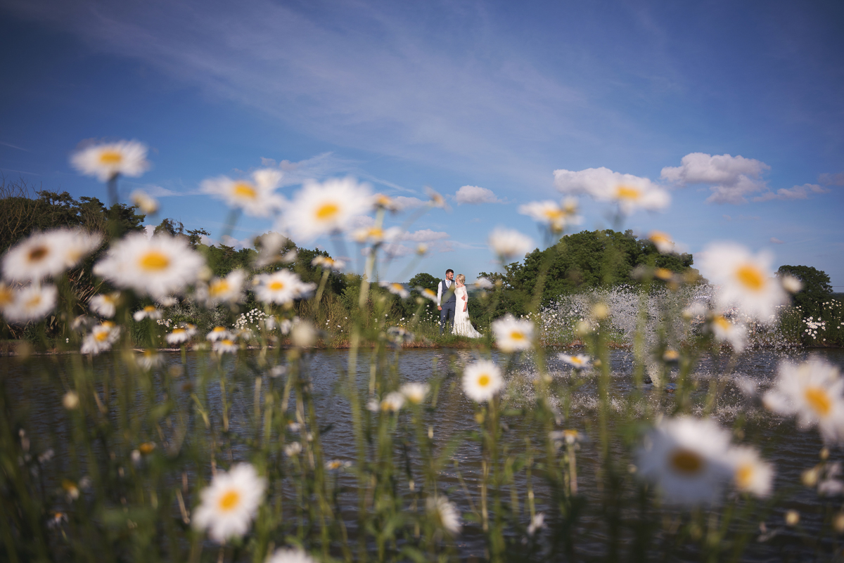 Bride and groom by the lake at Upton Barn wedding venue