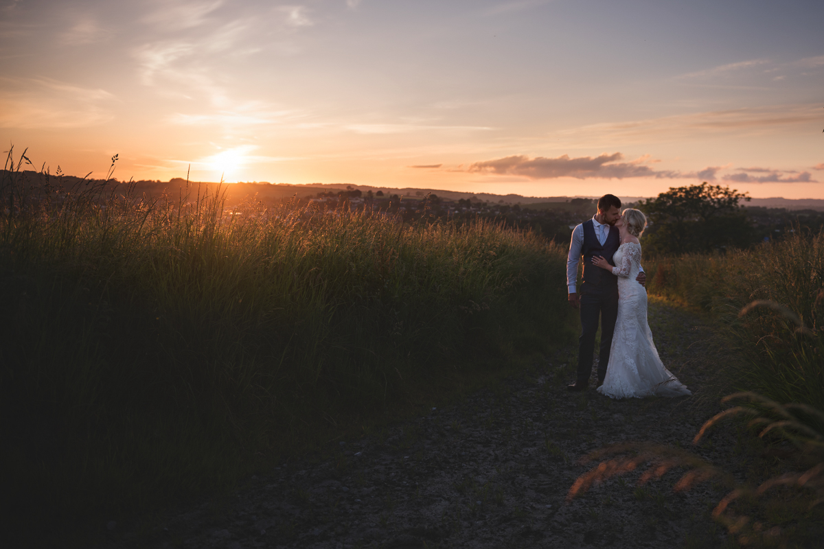 Bride and groom in a field at sunset at Upton Barn wedding venue