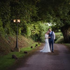 Bride and groom in the entrance lane of Upton Barn wedding venue