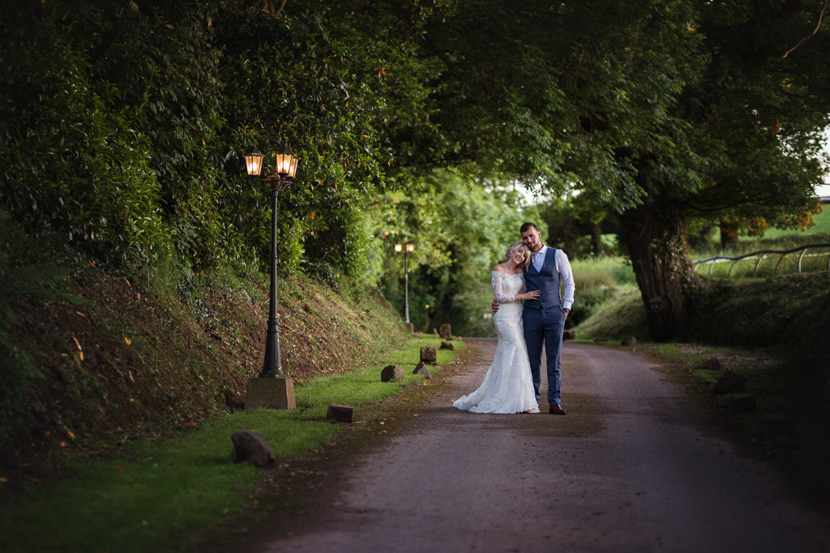 Bride and groom in the entrance lane of Upton Barn wedding venue