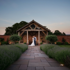 Bride and groom by the arbour at Upton Barn wedding venue