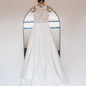 Wedding dress hangs in the Tack Room of Upton Barn & Walled Garden