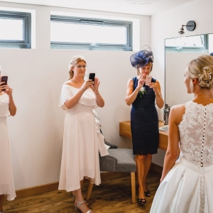 Bride is photographed by bridesmaids in The Tack Room at Upton Barn
