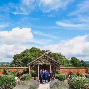 Groomsmens awaiting arrival of the bride at the arbor of Upton Barn & walled Garden