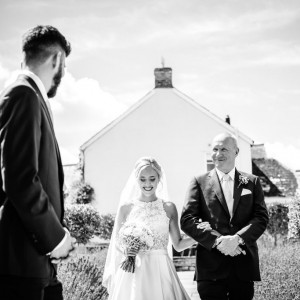 Father of the bride presents his daughter to the groom at the arbour in Upton Barns Walled Garden