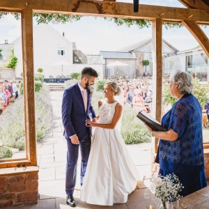 Registrar reads to the bride and groom at civil ceremony at Upton Barn & Walled Garden