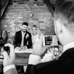 Friends take photos with their mobiles of the bride and groom in the arbour at Upton Barn & Walled Garden
