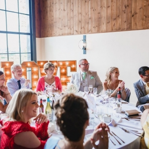 Happy guests dine at the wedding breakfast in The Stable Barn of Upton Barn & Walled Garden