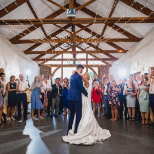 Bride and Grooms first dance in Cider Barn of Upton Barn & Walled Garden in front of family and friends