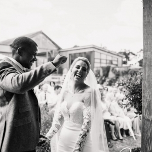 Groom punches the air with delight as he weds his bride in the walled garden