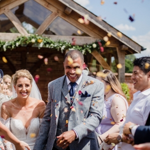 Bride and groom are covered with confetti as they walk back up the aisle in the walled garden
